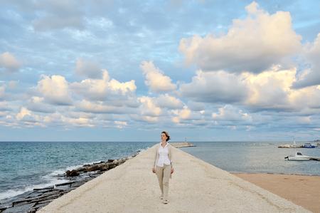 mujer caminando en el muelle - imagen conceptual libertad serenidad tranquilidad armonía positiva Foto de archivo