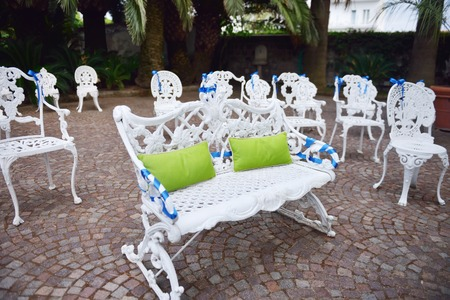 wedding chairs: Setting for outdoors wedding ceremony with white decorated chairs and bench for bride and groom
