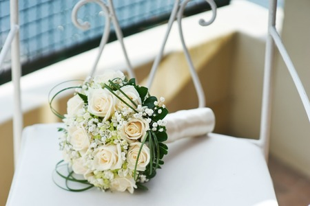 nuptial: Beautiful wedding bouquet of roses on a chair Stock Photo