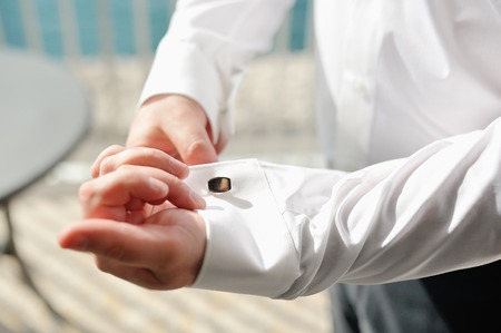 Groom fixing cufflinks of white shirt in wedding day