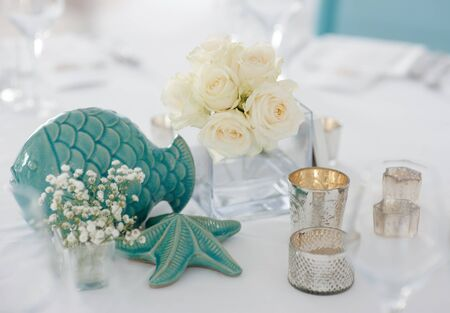 Wedding banquet decoration with white flowers and light blue porcelain fish