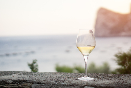 A glass of white wine, on background the sea of Massalubrense near Sorrento, Italy