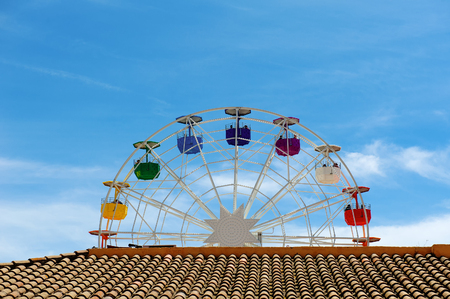 Brown roof, ferris wheel and blue sky day view