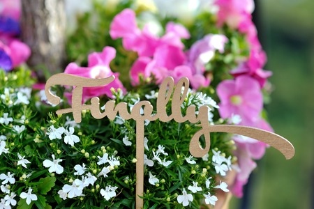 Finally word wedding decoration, on background colored flowers Stock Photo