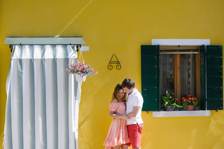 feelings and emotions: Tender couple near a yellow house in Burano island, Venice, Italy, Europe Stock Photo