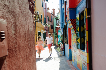 Travel couple walking down the alleys of Burano island, Venice, Italy, Europe Imagens