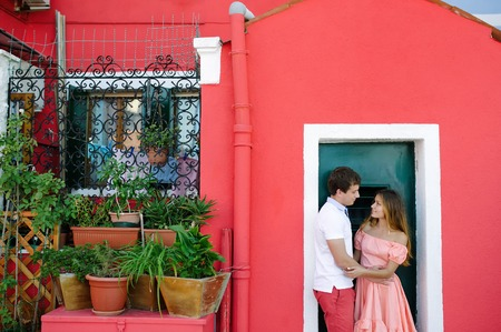 Tender couple in love near a typical Burano red house, Venice, Italy, Europe