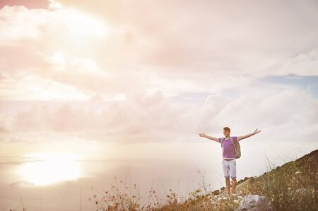 Young hiker with arms wide open on top of a mountain - freedom conquest concept