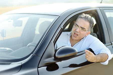 Road rage concept - irritated man screams and gestures while driving a black car