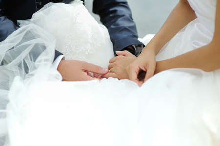 tenderly: Groom tenderly touching bride hand during wedding ceremony