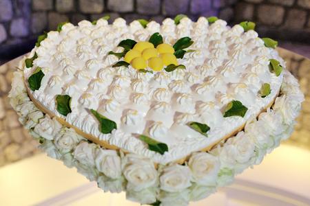 Beautiful heart shaped wedding lemon cake decorated with roses Stock Photo