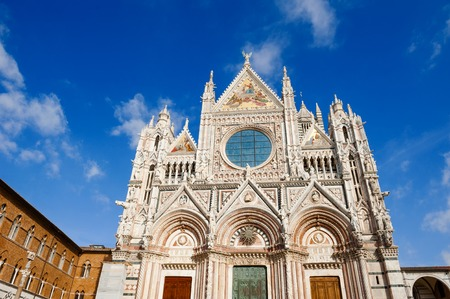 Scenic view of the facade of gothic renaissance church Santa Maria Assunta, cathedral of Siena, Tuscany, Italy, on background blue sky