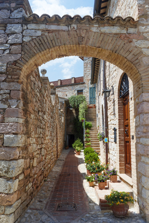 Old rocky arch over the street in Spello. The traditional italian medieval historic center in Umbria. Italy
