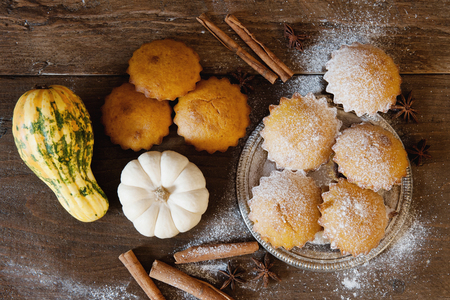 Homemade delicious pastry muffin with decorative pumpkin and cinnamon on wooden background Banco de Imagens