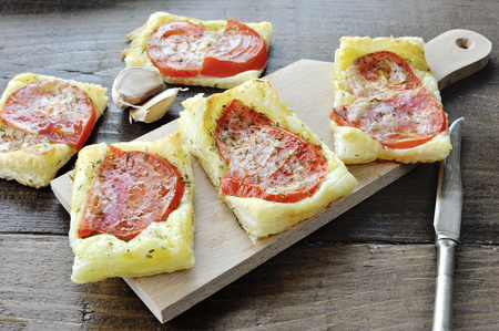 Pizza puff pastry with tomatoes and origan on a cutting board
