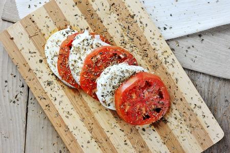 Tomato and mozzarella with origan - caprese salad italian food on chopping board Archivio Fotografico - 96894351