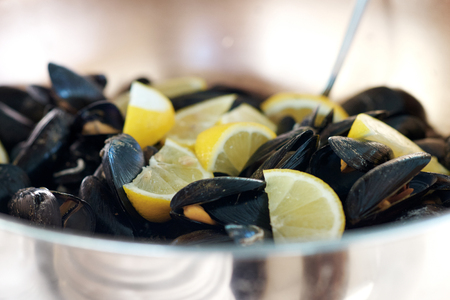 Delicious shellfish peppered mussels with pieces of lemon Stock Photo