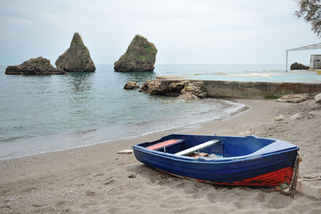 Fishing boat on Vietri sul Mare beach on background two large cliffs, a symbol of the city, province of Salerno, Campania, southern Italy Stock Photo