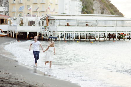 Young loving couple running along the beach, in the port of Sorrento, Italy. Imagens
