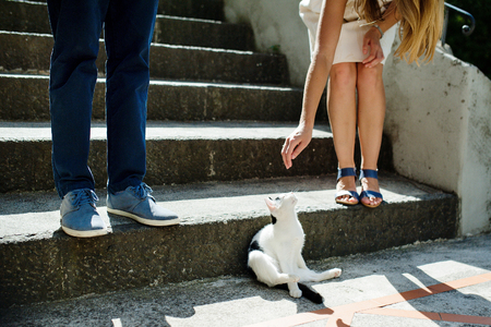 Young romantic couple playing with a cat in Positano, Italy. Popular travel destination.
