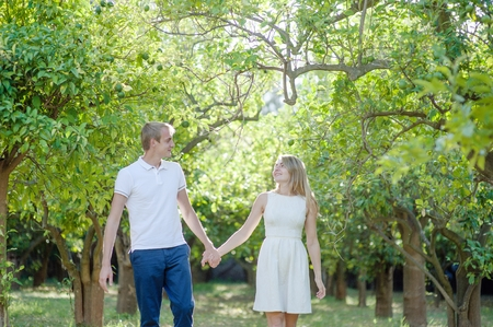 Young romantic couple walking holding hands on a lemon garden in Sorrento, Italy - love concept