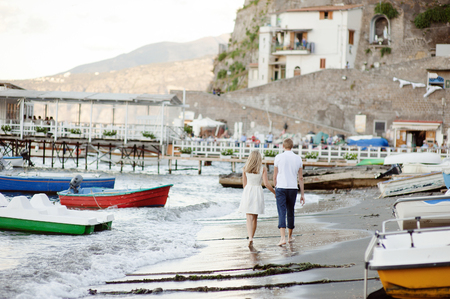 A young couple walks along the beach, in the port of Sorrento, Italy.