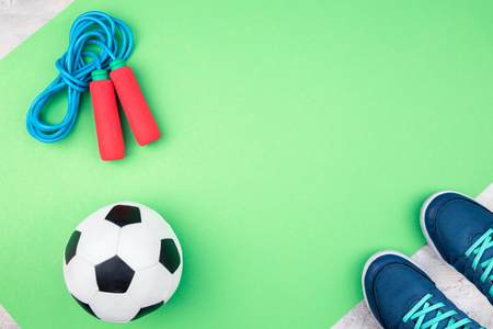 Kids soccer ball for football with jumping rope and soccer shoes on a light green mat flat lay style.