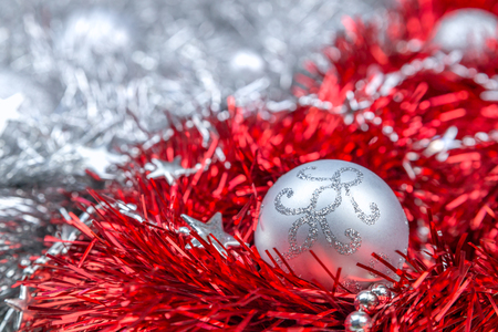 Silver Christmas ornaments on red tinsel