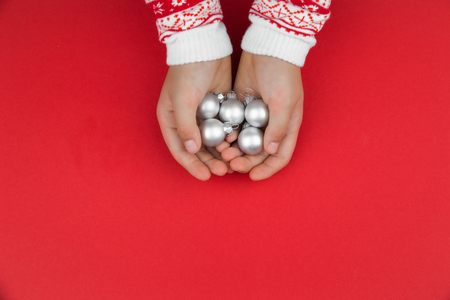 Child hands holding silver christmas baubles 写真素材