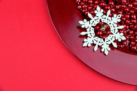 Red Christmas ornaments, beaded chain and wooden snowflake on red plate in flat lay style