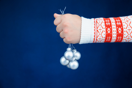 Child hand holding silver christmas baubles on blue background 写真素材