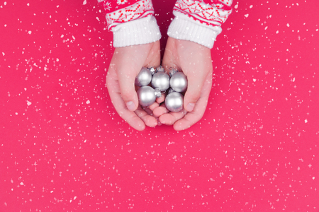 Child hand holding silver christmas baubles on red background