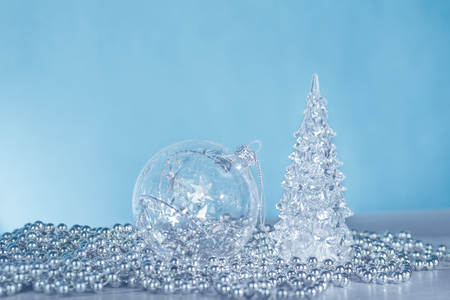 Silver and white Christmas ornaments: glass snowflake, bauble and christmas tree on blue background 写真素材