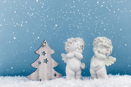 Two Christmas cherub baby angels statuettes on snow with wooden Christmas tree on light blue background