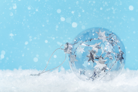 Crystal clear glass Christmas bauble with silver tinsel inside on white snow: on blue background with snow