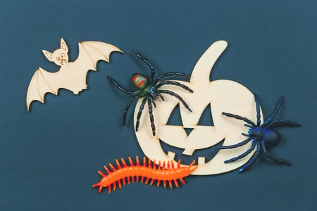 Do it yourself Halloween pumpkin and vampire bats cut outs on a colorful background in flat lay with paint and brush