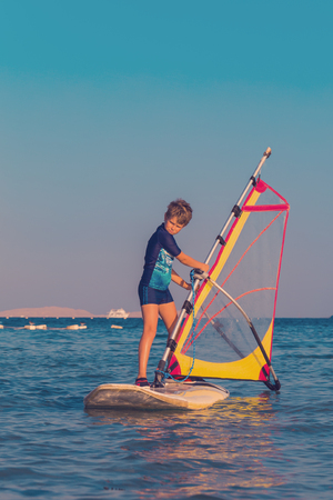 One child learning to windsurf in the sea at beautiful sunset light, close up