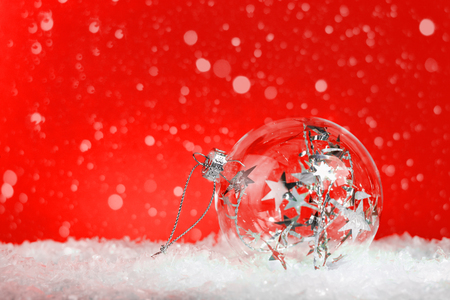Crystal clear glass Christmas bauble with silver tinsel inside on white snow: on red background with snow with copy space