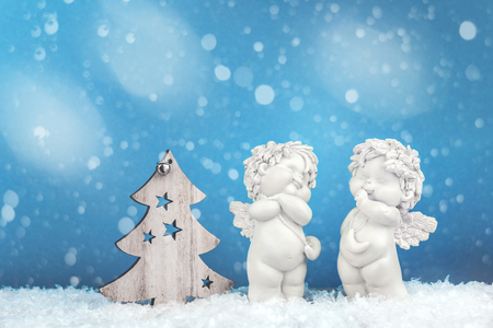 Two sweet Christmas cherub baby angels statuettes on snow with wooden Christmas tree on light blue background with snow, New Year concept Stockfoto