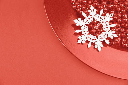 Christmas ornaments, beaded chain and wooden snowflake on a plate in flat lay style in living coral color year 2019