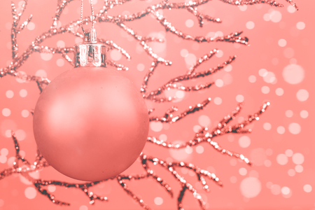 Shiny pastel coral Christmas decorations on silver branch against pink background, monochrome color with copy space
