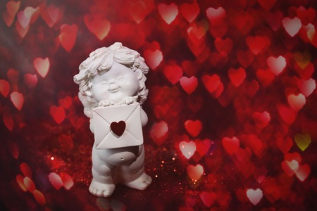 Cherub baby angel with heart and bokeh. St Valentine card, love and sentiment concept Banco de Imagens