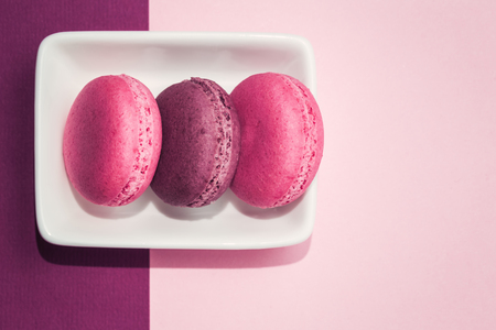 Several sweet tasty pink macarons in white bowl on pink background with copy space closeup