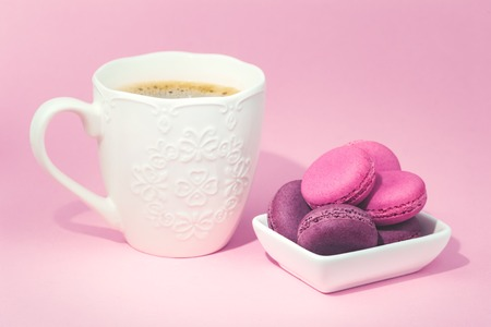 Several sweet tasty pink macarons in white bowl and white coffee mug on pink background with copy space closeup
