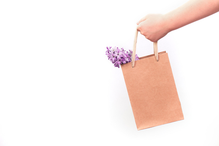 hand holding an eco paper bag with hyacinth flowers isolated. flare light. paper bag in hands