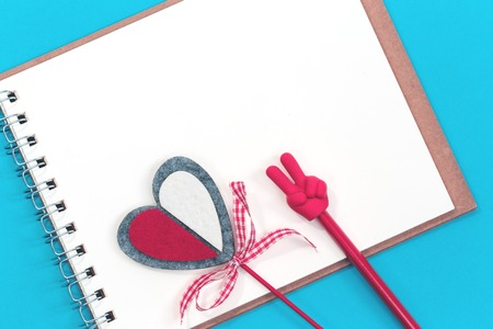 A red pencil with V sign, red crafted heart and a blank notepad on blue background. Flat lay with copy space