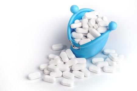 Tabletas blancas que caen del bolso azul, el consumo de seguridad de medicamentos y medicamentos y el concepto de costo con espacio de copia