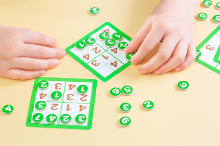 Hands of a child playing sudoku board game filling the card with number tokens. Education concept with copy space