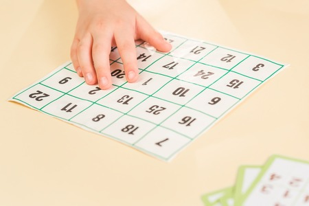 Hands of a child playing with numbers card board game. The card for children with dyslexia, finding numbers sequence teaching aid, with copy space