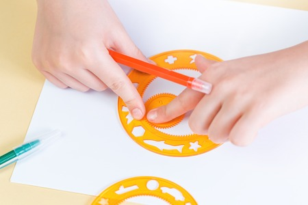 Hands of a child drawing with magic circles, education and board games concept with copy space